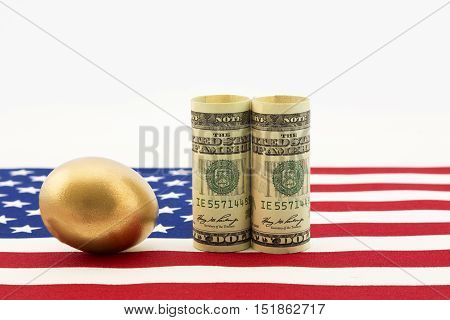 Gold nest egg with pair of American dollars placed on USA flag show success of national government policy and nation's business strength. Horizontal image with copy space.