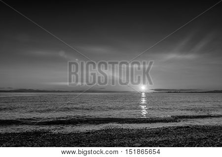 Point Roberts sunset at moonlight over the beach with cranes in background Washington State USA - black and white picture