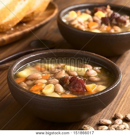 Traditional Hungarian Babgulyas (bean goulash) a soup made of pinto beans smoked meat potato carrot csipetke (homemade soup pasta) served in rustic bowls photographed with natural light (Selective Focus Focus on the meat)