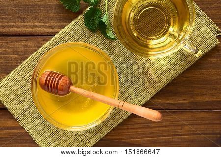 Honey in glass bowl with honey dipper fresh herbal tea above photographed overhead on wood with natural light