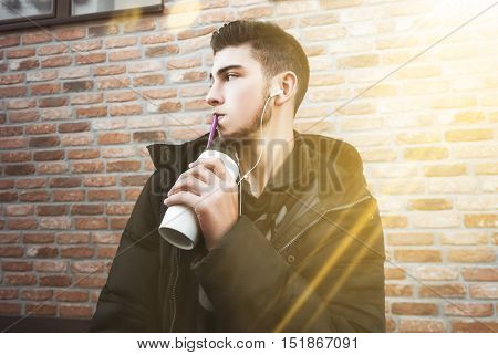 Cute young boy in jacket drinkers drink and listen to music. Sunny day. Funny mood.
