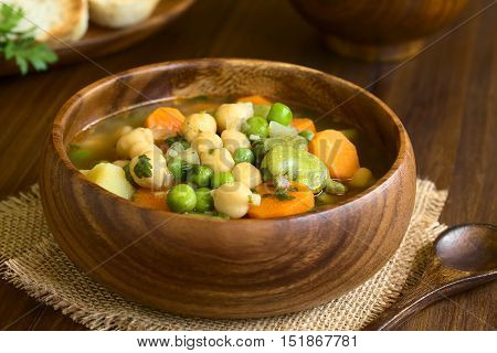 Vegetarian chickpea soup with carrot broad bean (fava bean) pea potato onion garlic and parsley served in wooden bowl photographed on wood with natural light (Selective Focus Focus one third into the soup)