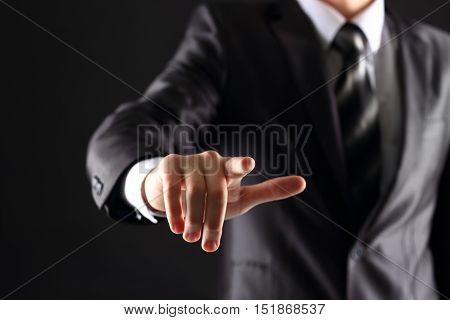 Businessman hand pressing an imaginary button on virtual screen
