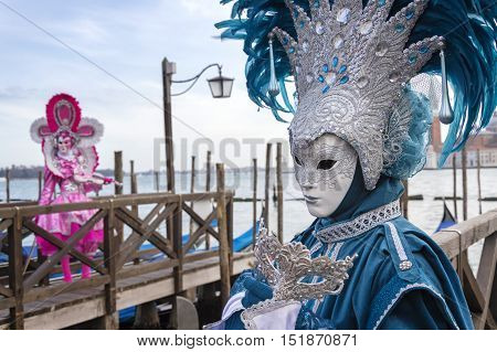 VENICE, ITALY - FEBRUARY 15, 2015:Two models disguised with colorful carnival costumes posing at a gondolas pier during the Carnival of Venice.