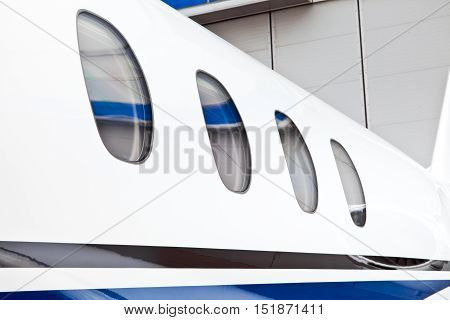 Four window portholes in a private jet plane