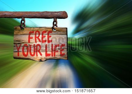 Free your life motivational phrase sign on old wood with blurred background