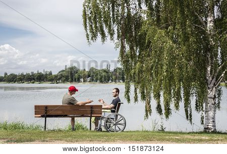 horizontal image of a father and a son in a wheel chair sitting in the distance next to a weeping willow tree and lake enjoying the beautiful sunshine on a summer day,