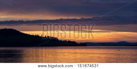 Silhouettes Of Trees On A Hill  Over Water