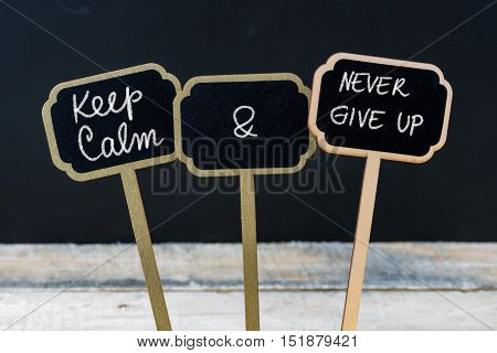 Keep Calm And Never Give Up Message Written With Chalk On Mini Blackboard Labels