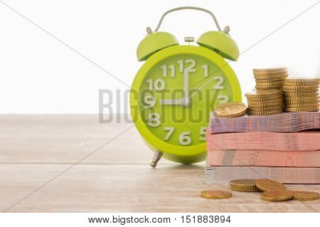 closeup money with clock on desk. concept of time is money Investment term.