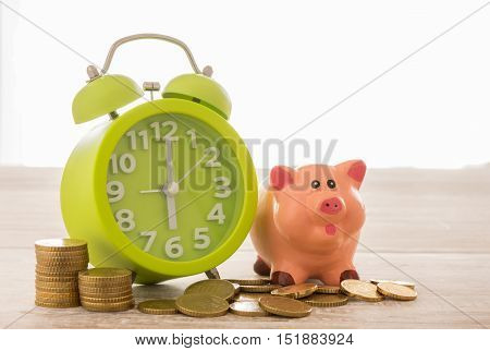 closeup clock with piggy bank coins on desk. concept of time is money save time save time and money.