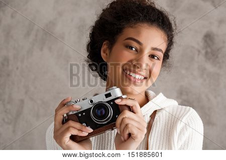Beautiful african female photograph smiling, holding camera over beige background. Copy space.