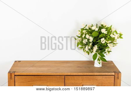 Commode with white flowers on white background