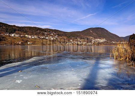 Lago di Serraia (Serraia lake) frozen in winter and the small town of Baselga di Pine Trentino Alto Adige Italy
