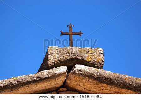 Detail of the roof of a typical house of Lessinia with a wrought iron cross against the blue sky. Verona Veneto Italy