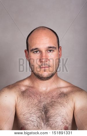 Portrait of serious shirtless man showing his hairy chest.
