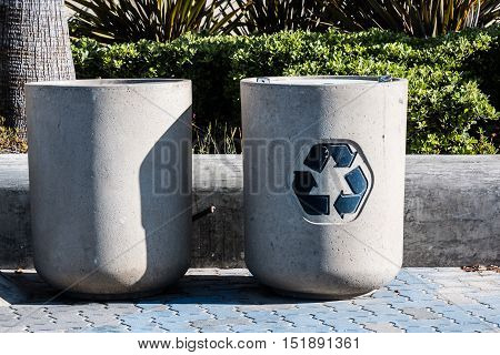 Two trash cans at a public park for disposal of standard waste and for recycling.