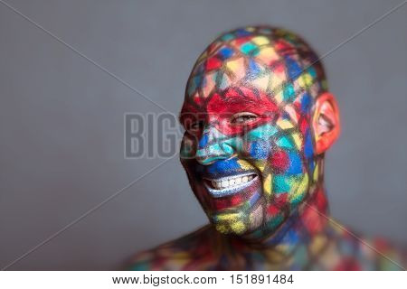 Malicious villain smiling portrait colorful face art with tilt shift and motion blur effect.