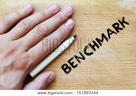 Human hand over wooden background and benchmark text concept