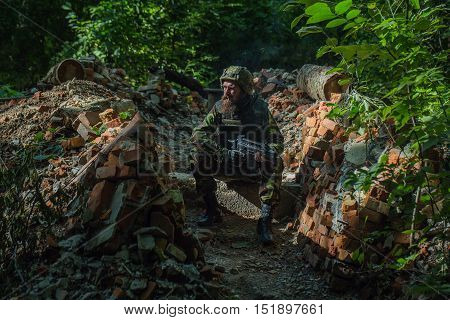 Soldier smokes in the barricade with the gun