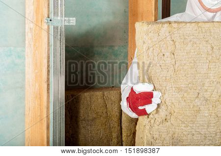 home attic insulation worker holding insulation material
