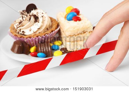 Female hand and tasty cakes on plate crossed with warning tape. Diet interruption concept