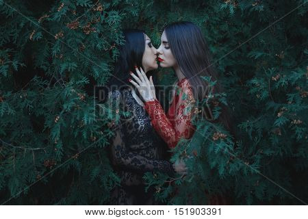 Lesbian kiss in nature among the trees.