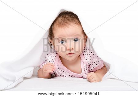 Portrait of a cute baby, lying under towel, isolated on white background