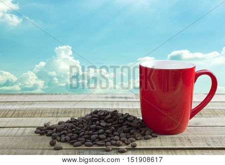 coffee beans and red cup on wooden table on sky background.