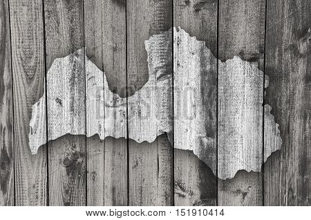 Map of Latvia on dark weathered wood