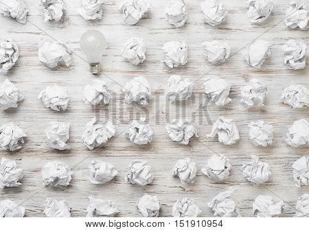 Many balls of crumpled paper and light bulb among them