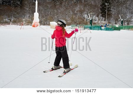 Teenage girl equipped for skiing on snowy slope at ski resort.