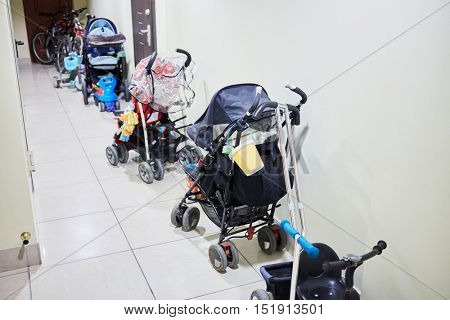 Row of baby carriages along the wall in the hallway.