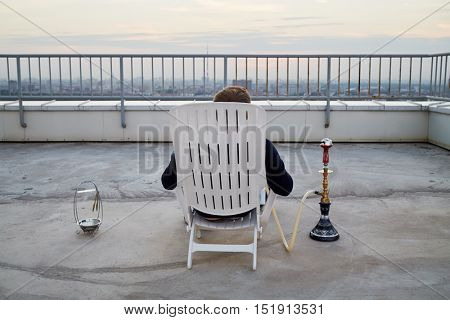 Man smoking hookah sitting on armchair on highrise roof at sunset, rear view.