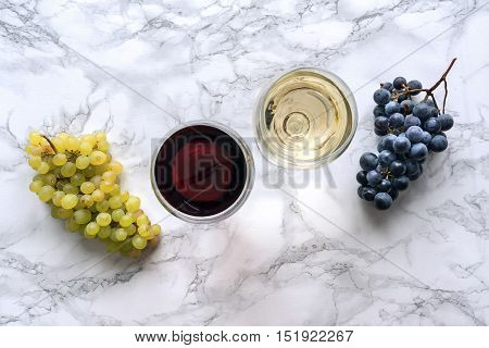 Red and white wine in the glass on marble table. Top view.