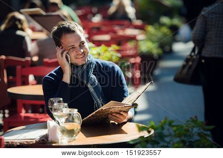 Man on cafe with smartphone talking and ordering something. Handsome young casual guy using mobile cell phone smiling happy sitting outdoors