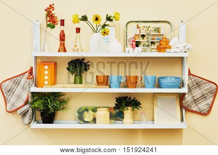 Home-made kitchen shelf with kitchenwear on the wall.