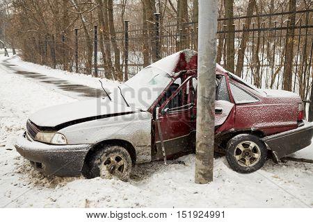 Damaged car crashing side into lamppost in winter.