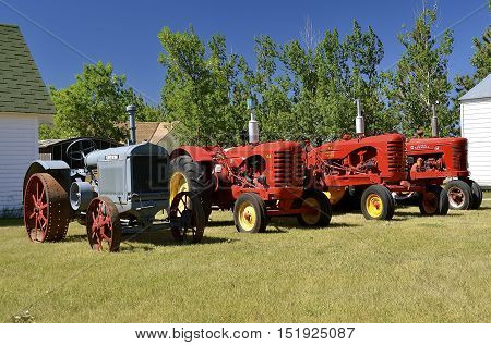 WATFORD CITY, NORTH DAKOTA, June 23, 2016: A vintage McCormick Deer, Massey Harris, and Formal M and tractors are displayed at the Watford City Pioneer Museum which is open and free to the public.