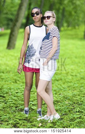 Teenagers Concept. Two Teenage Girfriends Standing Together in Forest Outdoors. African American Model and Caucasian Blond Model.Vertical Image
