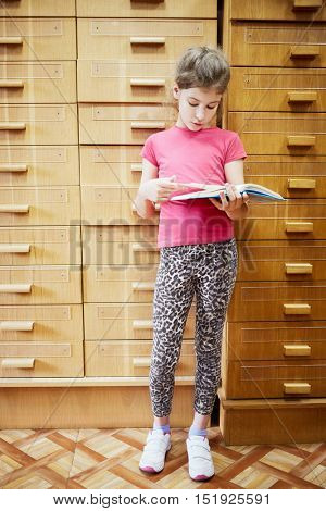 Teenage girl stands near file cabinet in library reading book.