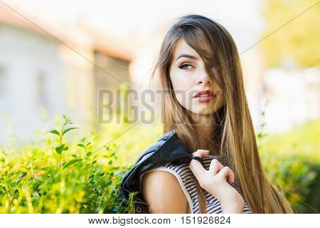 Gorgeous young woman with long blonde hair in park. Portrait of beautiful teenage girl posing outdoors on sunny day. Natural light, mild retouch.