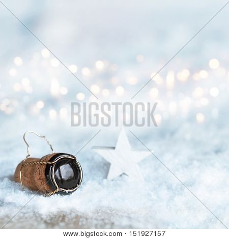 Winter motif for Christmas with a star and a champagne cork in the snow