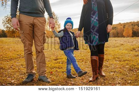 Mom dad and son holding hands togther.