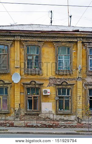 Fragment of fasade of old breaking wooden house in Samara, Russia. Traditional urban architecture with carved windows.