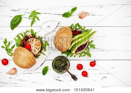 Fresh homemade two veggies burgers served on cutting board over white rustic table. Vegan grilled eggplant arugula sprouts and pesto sauce burger. Veggie beet and quinoa burger with avocado. Copy space. Top view overhead flat lay