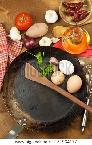 Kitchen iron pan and ingredients to prepare meals. Wooden spoons for cooking. Amenities of home cooking. Sales of kitchen tools.
