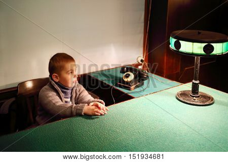 SAMARA, RUSSIA - MAY 8, 2015: Little boy (with model release) sits at table with green cloth and lamp in Stalins bunker