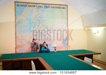 SAMARA, RUSSIA - MAY 8, 2015: Girls holding phone at table (models with releases) in Stalins bunker with big map