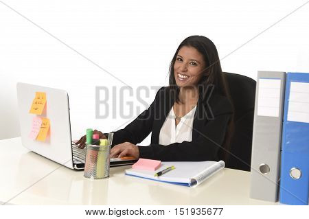 corporate portrait of young attractive hispanic businesswoman sitting at office desk working on computer laptop smiling happy and confident in successful female worker and business success concept